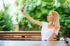 Le fotoet för ung flickadanandeselfie på smartphonen arkivfoton