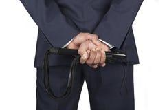 Le fouet en cuir s'est tenu par le maître dominant dans un costume Images libres de droits