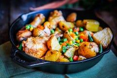 Le four a fait le poulet cuire au four avec des pommes de terre et des légumes sur le backgr en bois photographie stock