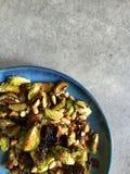 Le four a rôti des choux de bruxelles avec des pignons, ail, parmesan Photographie stock