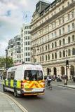 Le fourgon de police anglais passe le cycliste au feu de signalisation Image libre de droits
