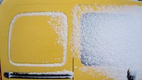 Le fourgon jaune compact congelé de voiture a couvert la neige au jour d'hiver Scène urbaine de la vie de ville en hiver image stock
