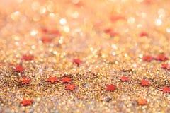 Le foyer mou et l'image sélective sur l'étoile rouge sur l'or allument le bokeh t Photos stock