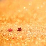 Le foyer mou et l'image sélective sur l'étoile rouge sur l'or allument le bokeh t photo libre de droits