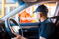 Le foyer sélectif à l'homme conduisant la voiture paye l'autoroute urbaine photos libres de droits