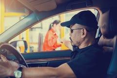 Le foyer sélectif à l'homme conduisant la voiture paye l'autoroute urbaine photographie stock libre de droits