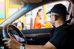 Le foyer sélectif à l'homme conduisant la voiture paye l'autoroute urbaine photographie stock