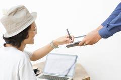 Le foyer sélectif de donner de main de vue supérieure se connectent le carnet avec l'ordinateur portable à l'arrière-plan photographie stock libre de droits