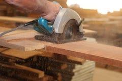 Le foyer sélectif sur le morceau de bois est coupé avec la scie circulaire électrique contre des mains de travailleur dans l'atel Image libre de droits