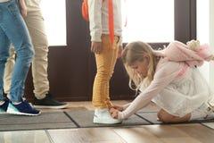 Le frère de aide de soeur pour attacher des chaussures attachent des dentelles, les enfants de mêmes parents f photo libre de droits