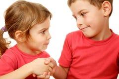 Le frère et la soeur avec le sourire se serrent la main Image libre de droits