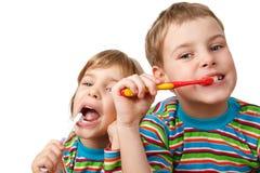 Le frère et la soeur dans des chemises se brossent les dents image stock