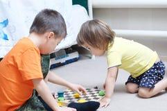 Le frère et la soeur jouant ensemble, des enfants de mêmes parents jouent à la maison sur des échecs Photographie stock libre de droits