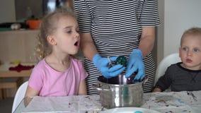 Le frère et la soeur regardant la prise de mère ont peint des oeufs de pâques de pot cardan clips vidéos