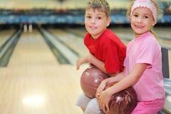 Le frère et la soeur s'asseyent dans le club de bowling Photographie stock