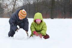 Le frère et la soeur sculpt le bonhomme de neige Images stock