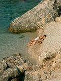 Le frère et les soeurs s'exposent au soleil sur la plage Photo libre de droits