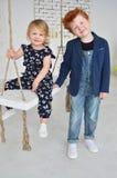 Le frère rouge d'enfants mignons et la soeur blonde ont un amusement sur l'oscillation Images stock