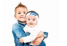 Le frère se tenant dessus remet sa petite soeur mignonne photographie stock libre de droits