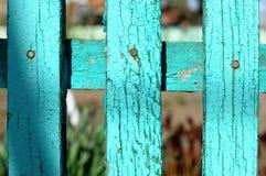 Le fragment d'une barrière rurale en bois faite à partir du vert peint a vieilli des planches sur le fond des usines de jardin da Photographie stock libre de droits
