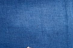 Le fragment des blues-jean naturelles d'abrégé sur plan rapproché donnent au fond une consistance rugueuse Photos stock