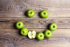 Le framsidan av gröna äpplen på en trätabell Apple emoticon royaltyfri bild