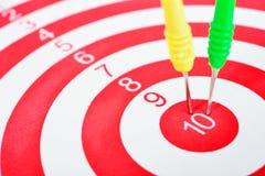 Le frecce dardeggiano colpire il centro di un obiettivo Immagine Stock