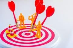 Le frecce dardeggiano colpire il centro di un obiettivo con la figura degli operai Immagine Stock