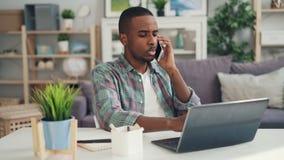Le free lance afroamericane infelici stanno parlando sul telefono cellulare che esprime le emozioni negative e che funziona con i stock footage