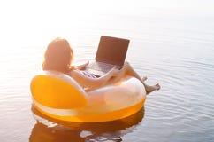 Le free lance lavorano ad un computer portatile che si siede in un anello gonfiabile in Th immagini stock