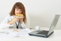 Le fretta della donna di affari fino a mangiano Immagine Stock