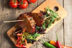 Le froid a bouilli le porc avec des tomates sur la table en bois Photos libres de droits