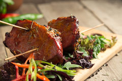 Le froid a bouilli le porc avec des tomates sur la table en bois Photo stock