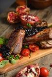 Le froid a bouilli le porc avec des tomates sur la table en bois Photographie stock libre de droits