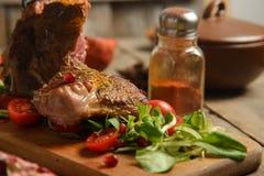 Le froid a bouilli le porc avec des tomates sur la table en bois Photographie stock