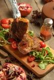 Le froid a bouilli le porc avec des tomates sur la table en bois Images stock