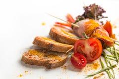 Le froid a bouilli le porc avec des tomates sur un fond blanc Image stock