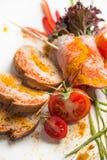 Le froid a bouilli le porc avec des tomates sur un fond blanc Photos libres de droits