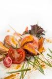 Le froid a bouilli le porc avec des tomates sur un fond blanc Photo stock