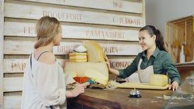 Le fromage amical de vendeur conseille l'acheteur Il devrait être derrière le compteur au sujet des fromages plus grands banque de vidéos