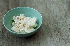 Le fromage blanc avec le fruit dans un plat vert est sur la table image libre de droits