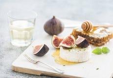 Le fromage de camembert ou de brie avec les figues, le nid d'abeilles et le verre frais de vin blanc sur la portion embarquent au photographie stock