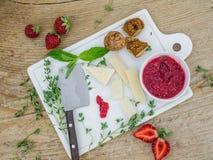 Le fromage et le fruit ont placé sur un bureau en bois Image stock