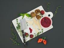 Le fromage et le fruit ont placé sur une surface foncée Photo stock