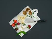 Le fromage et le fruit ont placé sur une surface foncée Photographie stock libre de droits