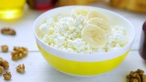 Le fromage friable et blanc de petit déjeuner sain - avec la banane, les noix, les croissants, le miel et l'airelle bloquent dans banque de vidéos