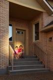 Le frère et la soeur s'asseyent sur des escaliers près de la trappe Photo stock