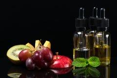 Le fruit assaisonne des liquides pour les cigarettes électroniques, concept sur un fond noir photographie stock libre de droits