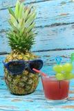 Le fruit d'ananas avec les lunettes de soleil bleues boit le cocktail fruité Photographie stock