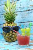 Le fruit d'ananas avec les lunettes de soleil bleues boit le cocktail fruité Images libres de droits